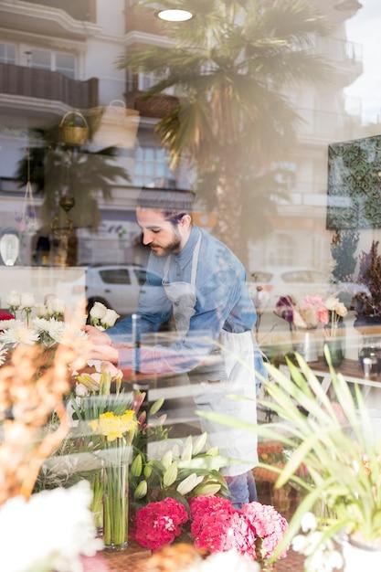 Mannelijke bloemist die de bloemen schikt die door het glas in de bloemwinkel worden gezien Gratis Foto