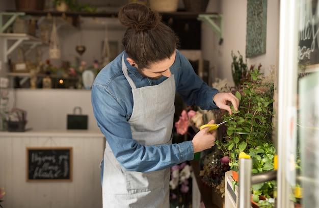 Mannelijke bloemist die de installatie in de bloemwinkel snoeit Gratis Foto