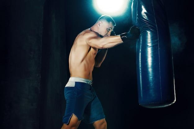 Mannelijke bokser boksen in bokszak Gratis Foto