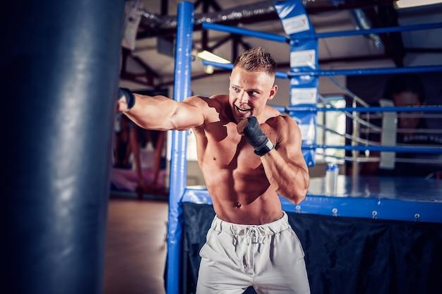 Mannelijke bokser die traint met bokszak in donkere sporthal. jonge bokser die op bokszak traint. Premium Foto