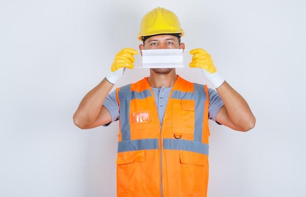 Mannelijke bouwer die medisch masker over gezicht in uniform, helm, handschoenen, vooraanzicht houdt. Gratis Foto