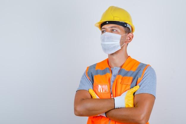 Mannelijke bouwer in uniform, helm, handschoenen, masker wegkijken met gekruiste armen en voorzichtig, vooraanzicht kijken. Gratis Foto