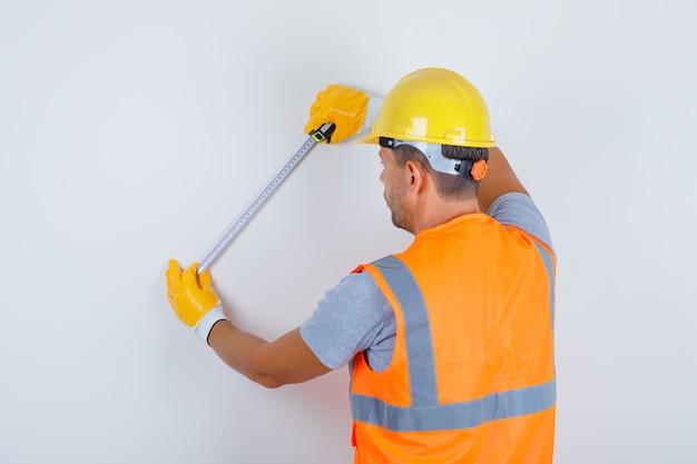 Mannelijke bouwer met behulp van meetlint op muur in uniform, helm, handschoenen en op zoek naar drukke, achteraanzicht. Gratis Foto