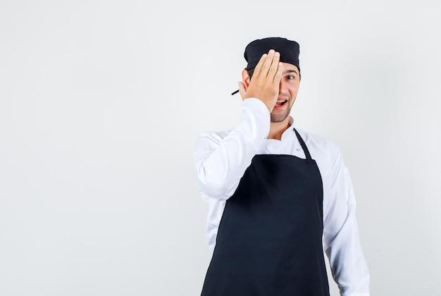 Mannelijke chef-kok die één oog bedekt met dient uniform, schort in en kijkt vrolijk, vooraanzicht. Gratis Foto