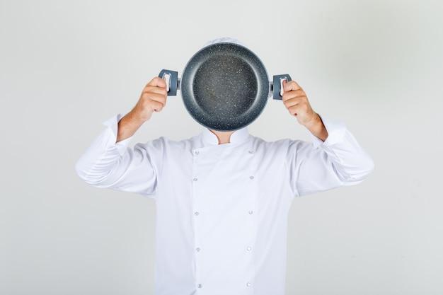 Mannelijke chef-kok die lege pan over zijn gezicht in wit uniform houdt Gratis Foto