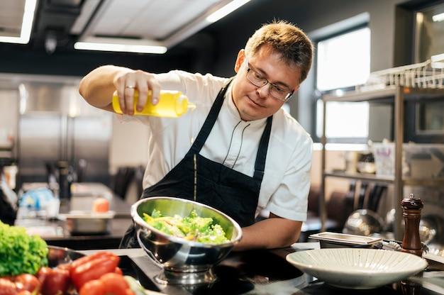 Mannelijke chef-kok die olie in salade toevoegt Premium Foto