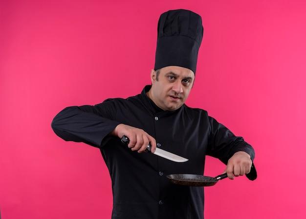 Mannelijke chef-kok dragen zwarte uniform en koken hoed met pan en mes kijken naar camera met ernstig gezicht staande over roze achtergrond Gratis Foto