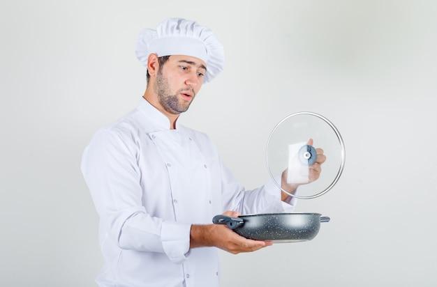 Mannelijke chef-kok in wit uniform glazen deksel van pan openen en verbaasd kijken Gratis Foto