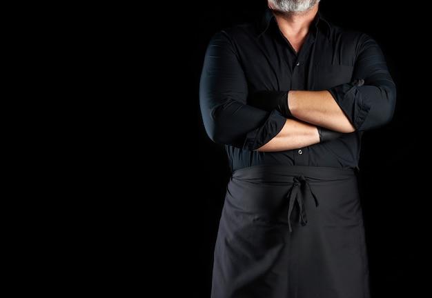 Mannelijke chef-kok in zwart uniform stak zijn armen voor zijn borst op een zwarte achtergrond, banner voor restaurants en cafés, lege ruimte voor een inscriptie Premium Foto