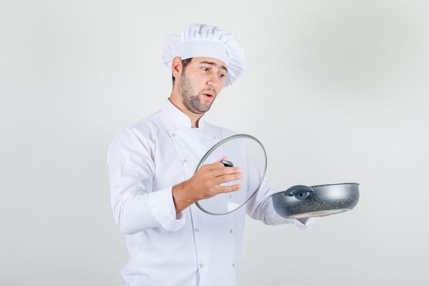 Mannelijke chef-kok pan en glazen deksel in wit uniform houden en verbaasd kijken. Gratis Foto