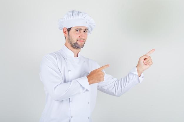 Mannelijke chef-kok wijzende vingers weg in wit uniform en op zoek positief Gratis Foto