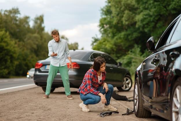 Mannelijke en vrouwelijke chauffeurs schreeuwen na auto-ongeluk op de weg. auto-ongeluk. kapotte auto of beschadigd voertuig, auto-botsing op snelweg Premium Foto