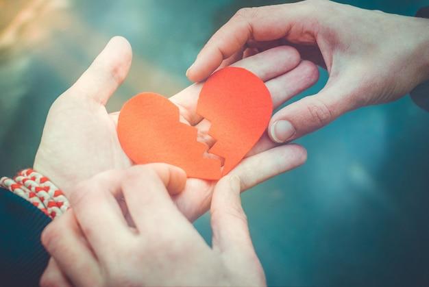Mannelijke en vrouwelijke handen die een gebroken hart herstellen. scheidingsconcept. hou van concept Premium Foto