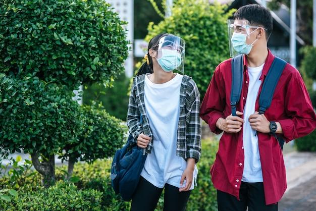 Mannelijke en vrouwelijke studenten dragen een chill gezicht en maskers. loop over het voetpad Gratis Foto