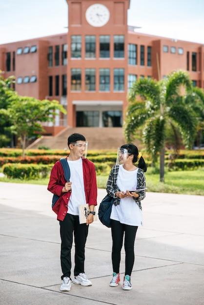 Mannelijke en vrouwelijke studenten dragen een gezicht chill en staan voor de universiteit. Gratis Foto
