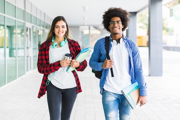 Mannelijke en vrouwelijke studentenholdingsboeken die ter beschikking in universiteitsgang lopen Premium Foto
