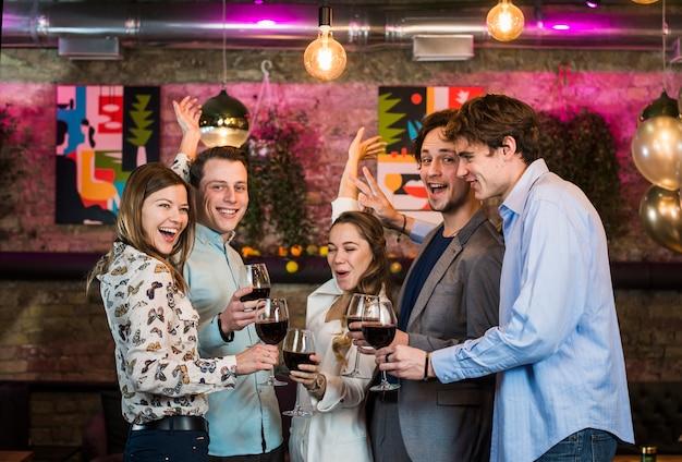 Mannelijke en vrouwelijke vrienden die van dranken genieten terwijl het dansen in bar Gratis Foto