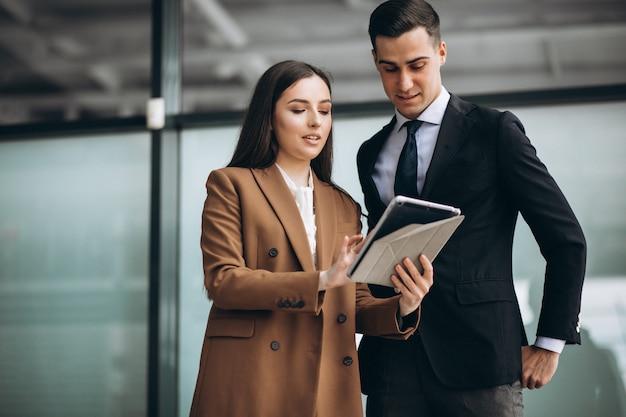 Mannelijke en vrouwelijke zakenmensen werken op tablet in office Gratis Foto