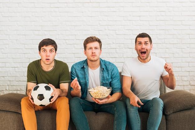 Mannelijke fans die op een voetbalwedstrijd op tv thuis letten Gratis Foto