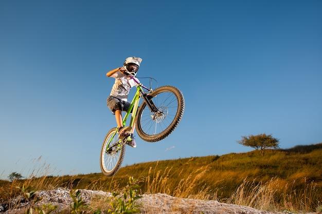 Mannelijke fietser die gevaarlijke sprong op een bergfiets maken op de helling tegen blauwe hemel Premium Foto