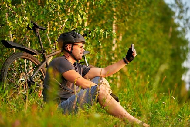Mannelijke fietser in een helm zit op het gras naast een fiets en neemt een selfie. Premium Foto