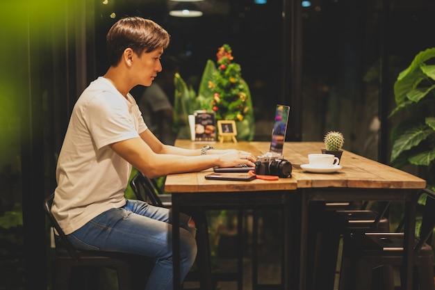 Mannelijke freelancer die aan laptop bij late nacht in koffiewinkel werken. Premium Foto