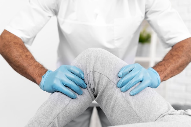 Mannelijke fysiotherapeut die de mobiliteit van de knie van de vrouw controleert Gratis Foto