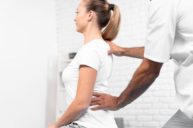 Mannelijke fysiotherapeut die de rug van de vrouw controleert Gratis Foto