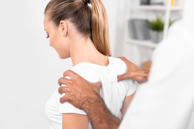 Mannelijke fysiotherapeut die de rugschouders van de vrouw controleert Gratis Foto