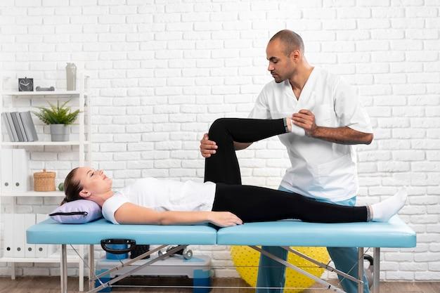 Mannelijke fysiotherapeut die het been van de vrouw controleert Gratis Foto