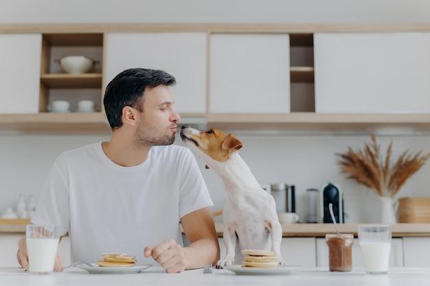 Mannelijke gastheerkussen met hond, eet smakelijke pannenkoeken Premium Foto