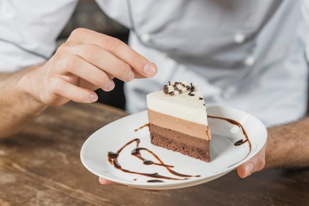 Mannelijke gebakjechef-kok die dessert in de keuken verfraaien Gratis Foto