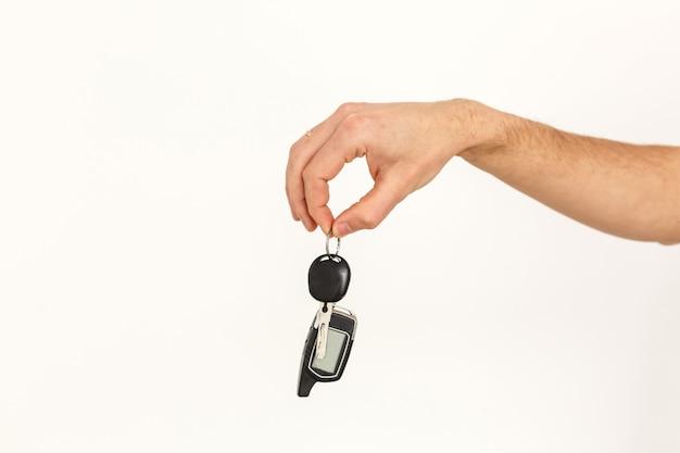 Mannelijke hand die een autosleutel houdt die op wit wordt geïsoleerd Premium Foto