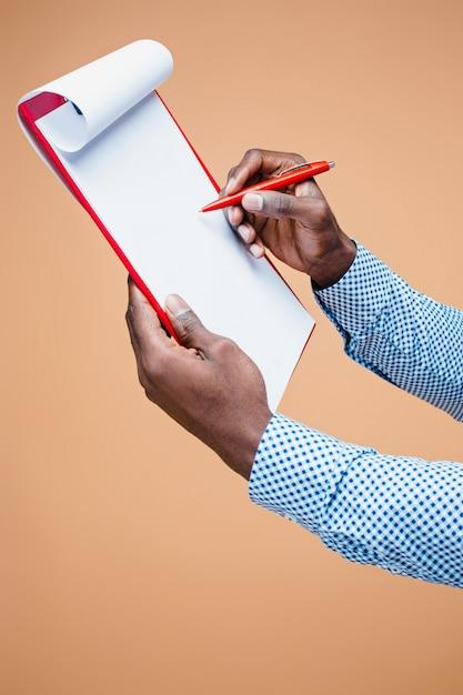 Mannelijke hand die op leeg geïsoleerd klembord schrijft ,. Gratis Foto