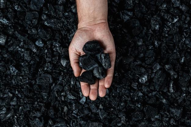 Mannelijke hand met steenkool op de achtergrond van een hoop steenkool, mijnbouw in een open kuilgroeve, exemplaarruimte. Premium Foto