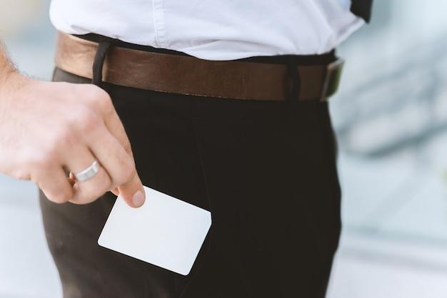 Mannelijke hand met wit leeg adreskaartje dichtbij zak, close-upfoto met selectieve nadruk Premium Foto