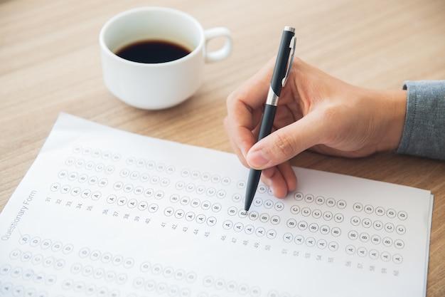Mannelijke hand te beantwoorden vragenlijst vorm met pen Gratis Foto