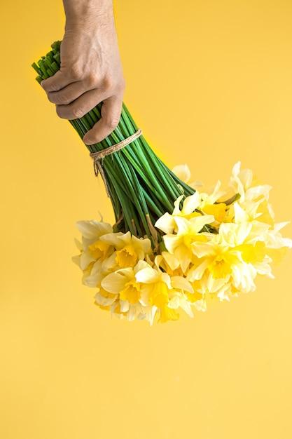 Mannelijke handen als achtergrond met een boeket van bloemen. Gratis Foto