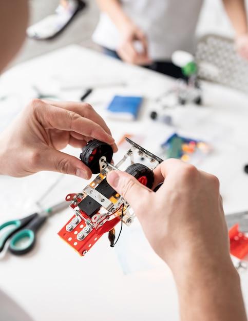 Mannelijke handen bouwen van robotauto's in de werkplaats Premium Foto