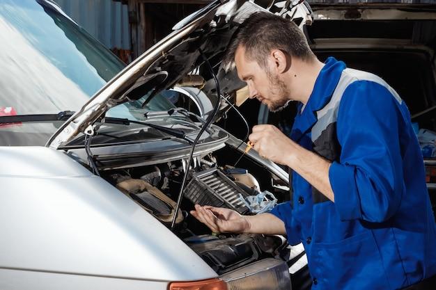 Mannelijke handen close-up, controleert het oliepeil in de motor. Premium Foto