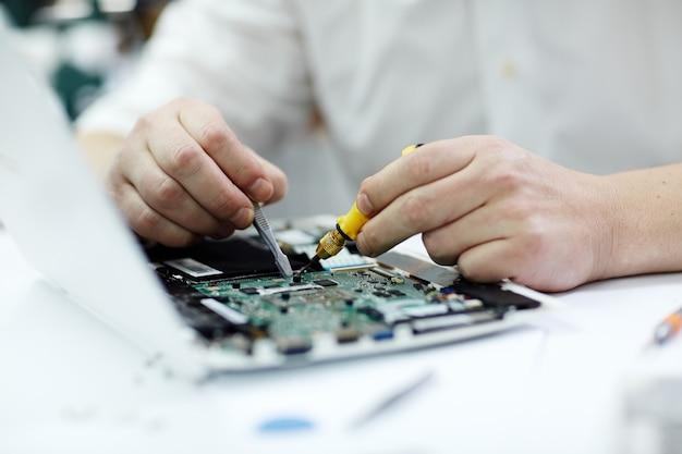 Mannelijke handen die laptop herstellen Gratis Foto