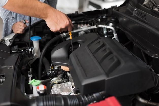 Mannelijke handen die motor van een auto controleren Gratis Foto