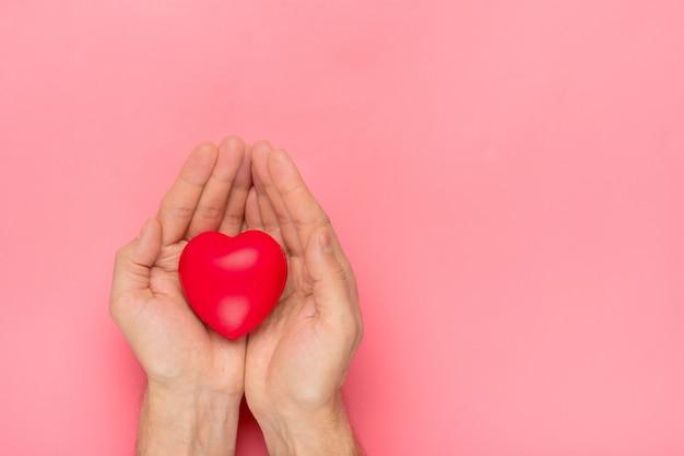 Mannelijke handen met rood hart in handen op roze achtergrond happy valentine's day Premium Foto