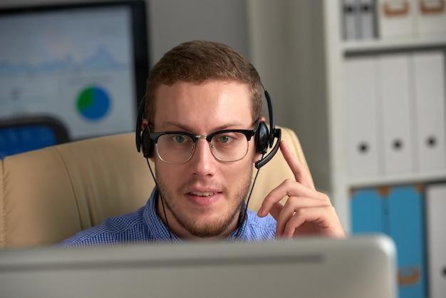 Mannelijke hotline-operator die in callcenter met hoofdtelefoon werkt Gratis Foto