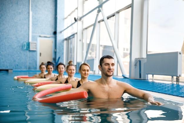 Mannelijke instructeur en vrouwelijke zwemmers groep, aquarobics training in het zwembad. man en vrouw in het water, sport zwemmen fitnesstraining Premium Foto