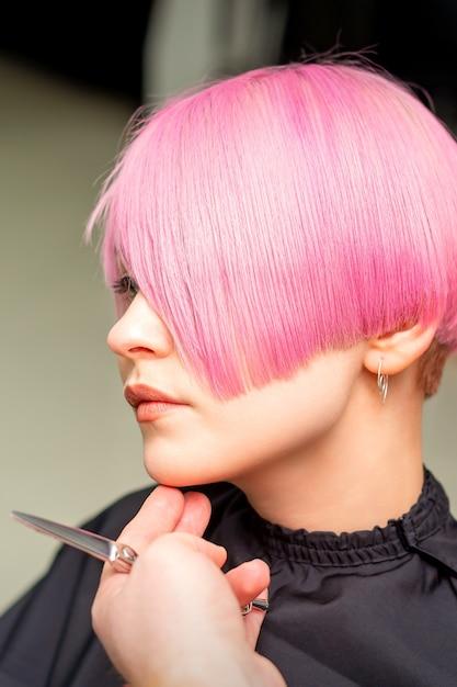 Mannelijke kapper maakt kort roze kapsel voor een jonge blanke vrouw in een schoonheidssalon Premium Foto
