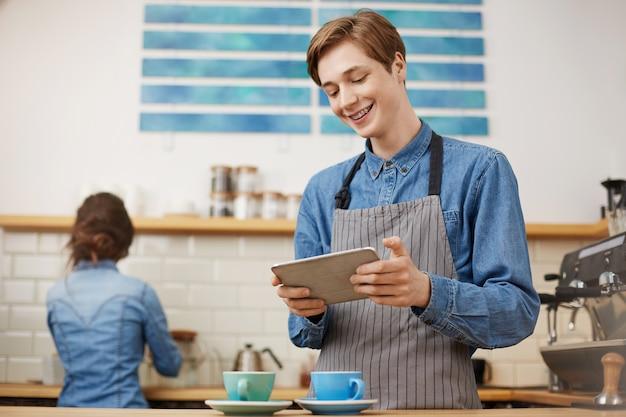 Mannelijke kassier die bestellingen nemen die lusje gebruiken bij heldere koffiewinkel. Gratis Foto