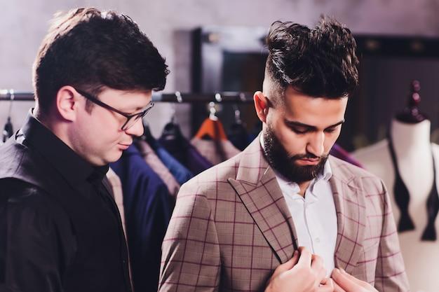 Mannelijke klant bij winkelcomplex die bedrijfskleren proberen die door winkelmedewerker wordt geholpen Premium Foto