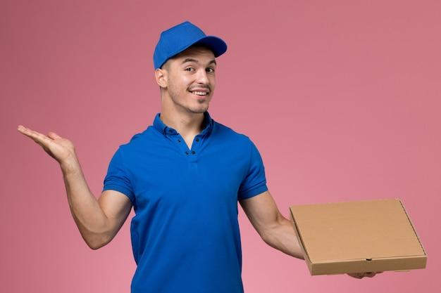 Mannelijke koerier in blauw uniform bedrijf bezorgdoos met voedsel met glimlach op roze, werknemer uniforme dienstverlening Gratis Foto