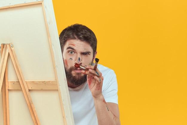 Mannelijke kunstenaar puttend uit ezel op geel Premium Foto